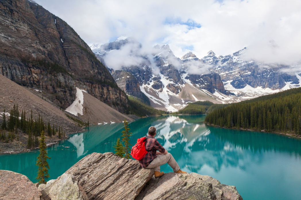 man sitting alone with lake and mountains in canada