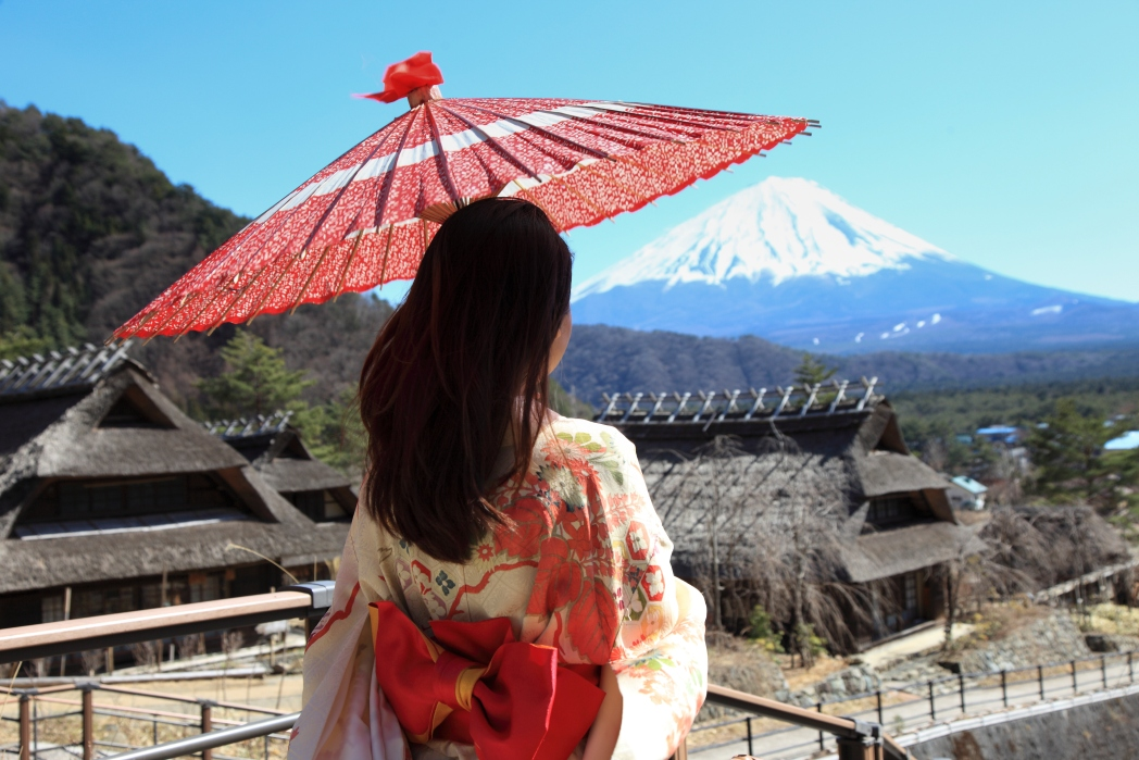 woman standing with umbrella in tokyo with mountain in background